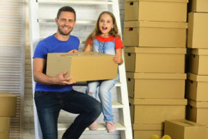 Dad and daughter packing boxes for a traditional storage unit